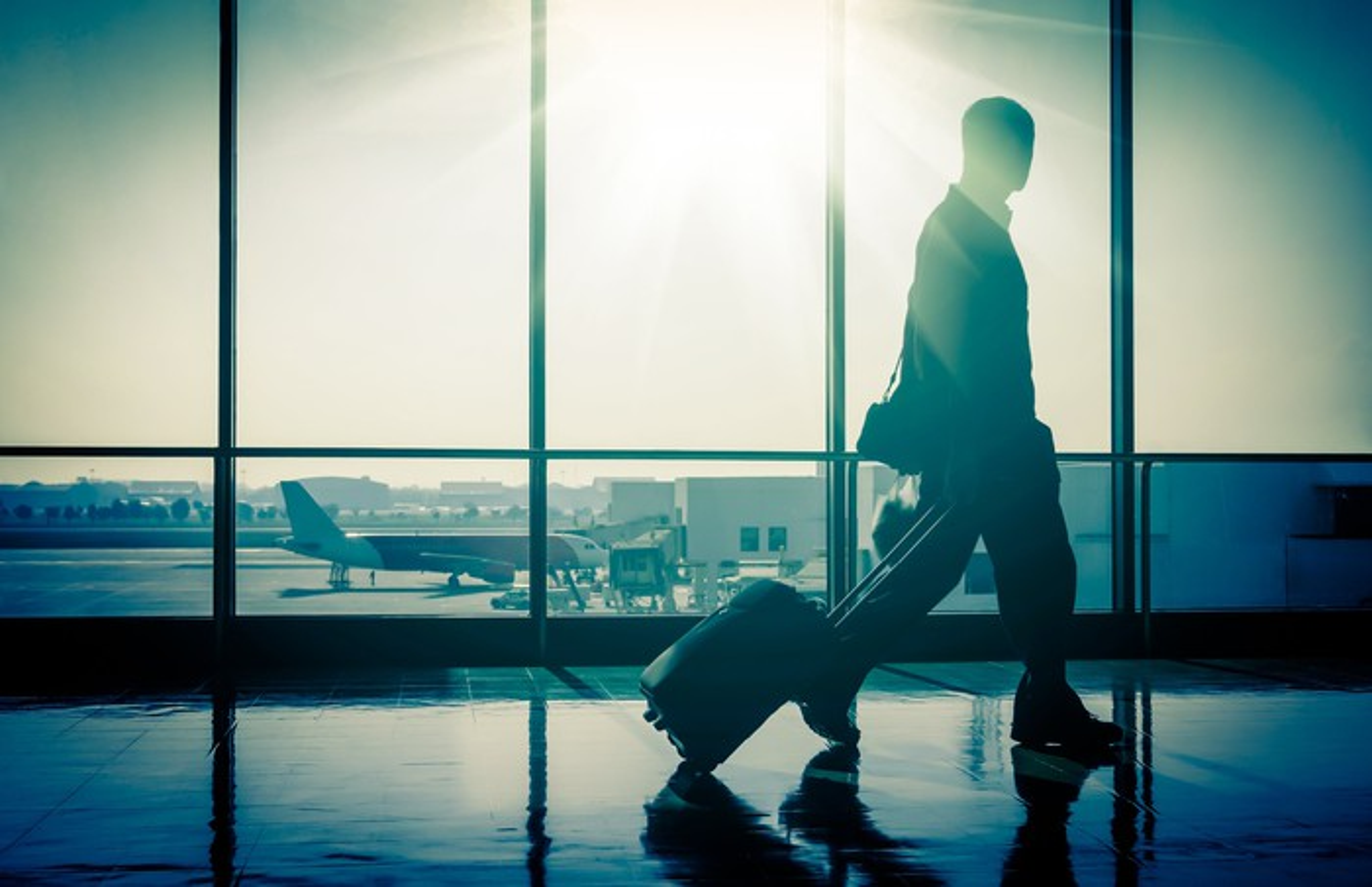 Man rolling suitcase through airport