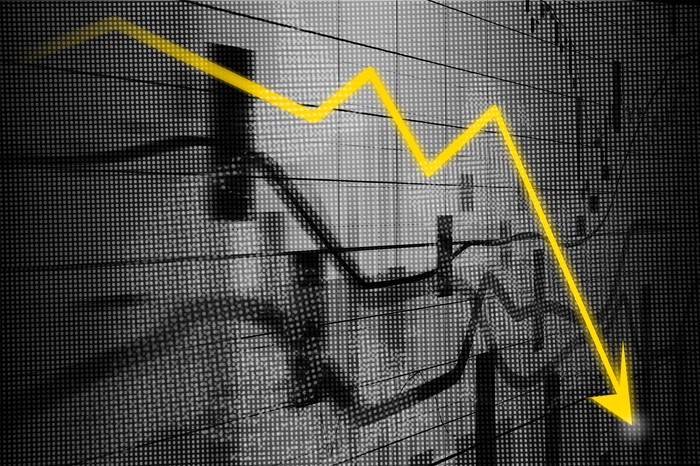 Yellow charting arrow headed abruptly downward, set against a grayscale array of unclear charts.