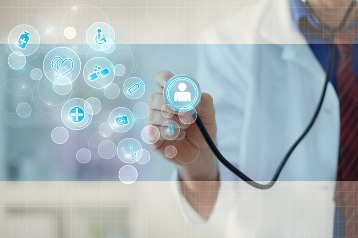 A doctor holding a stethoscope up to an illustrated bubble with a person in it, representing virtual healthcare.
