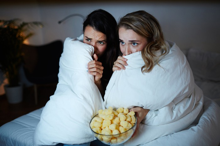 Two young women hide beneath a blanket