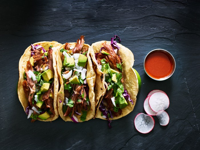 Three tacos on a table next to sauce and radishes.