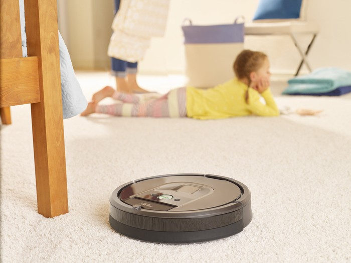 iRobot Roomba 980 cleaning carpet in a home, while a child lies on the floor nearby.