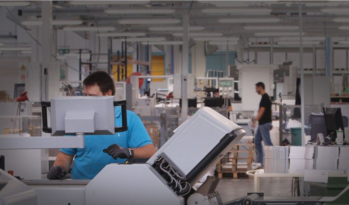 Workers using Cimpress' mass-customization platform