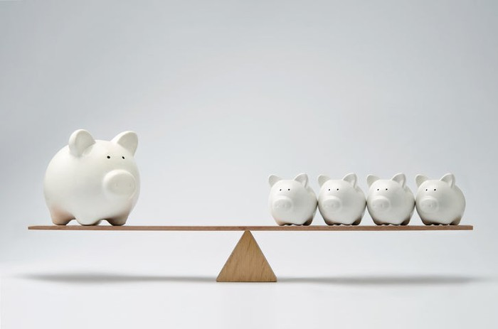 A balance with one large piggy bank on one side and four smaller piggy banks on the other.
