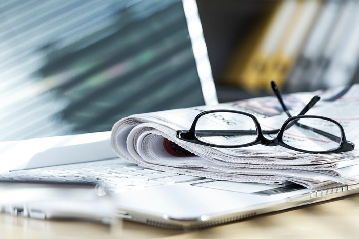 Folded newspaper and reading glasses resting on a laptop.