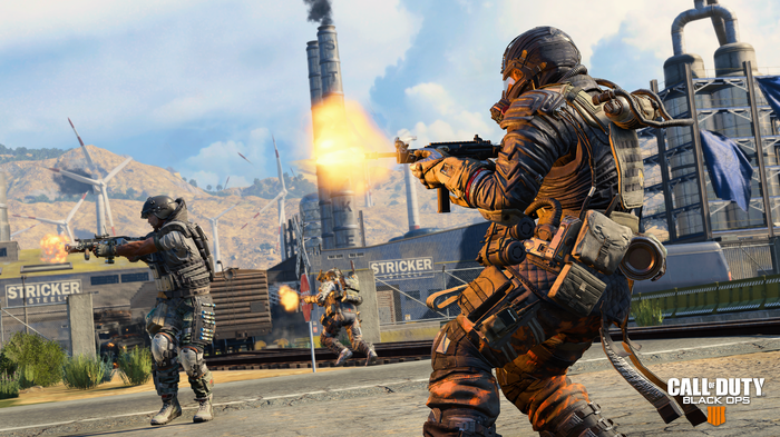 Screenshot of Activision's Call of Duty Black Ops 4 game depicting two in-game soldiers standing in an industrial area and firing weapons.