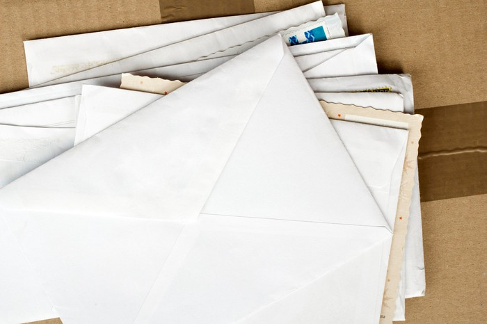 Bird's-eye view of a stack of envelopes on top of a cardboard shipping box.