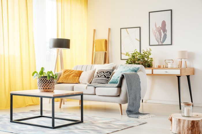 A living room that includes a plant on a table, a lamp, yellow curtains, framed art on the wall, and pillows on a sofa