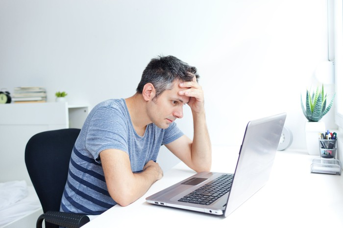 Man at laptop holding his head.
