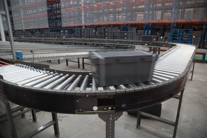A bin moves on a conveyor belt in a warehouse