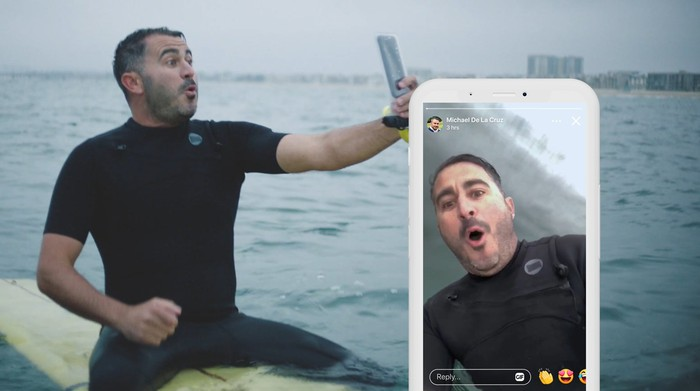 A man on a surfboard taking a video of himself with his smartphone. Screenshot of the video on a smartphone.