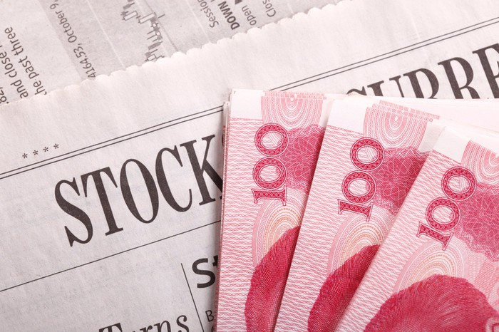 Chinese yuan notes lying on a newspaper stocks section.