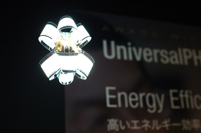 """Contemporary lamp made of curved, flexible OLED panels with """"UniversalPHOLED"""" and """"Energy Efficient"""" on a banner in the background."""