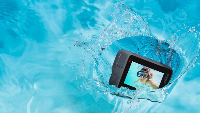 GoPro's HERO7 Silver camera falling into blue water with an image of a scuba diver on its display