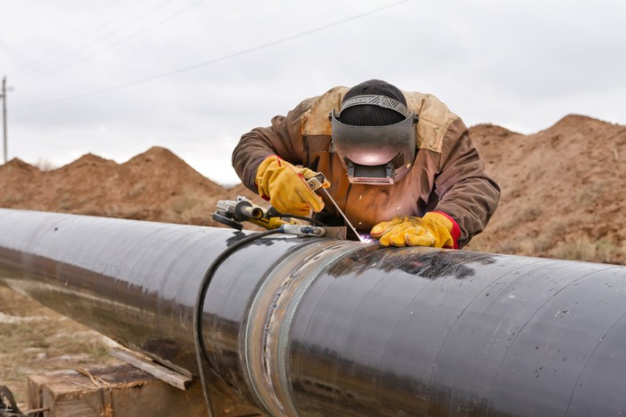 Person in welding gear welding two parts of a pipeline together, with dirt piles behind.