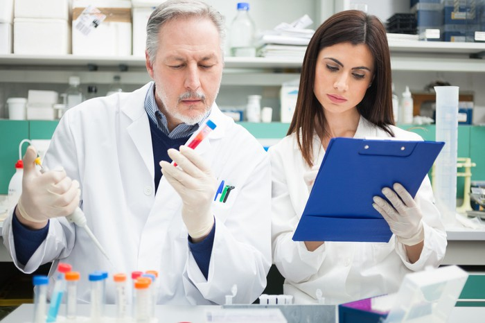 Two lab researchers examining red fluid in test tubes and making notes on a clipboard.