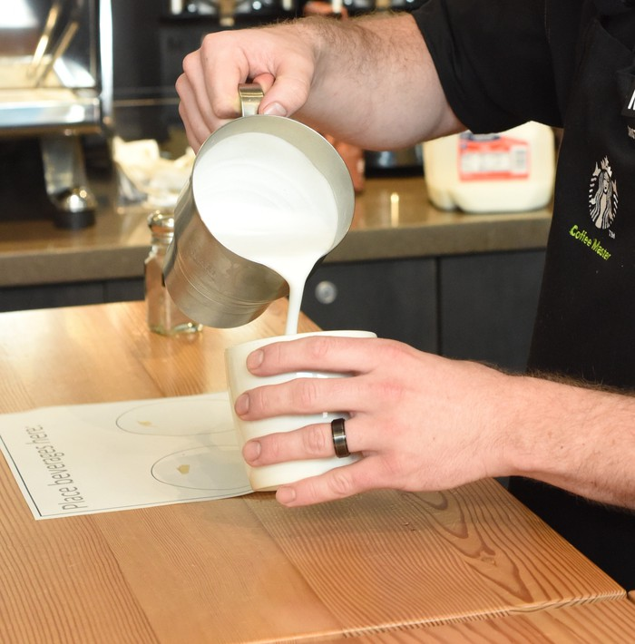 A Starbucks barista pours a drink.