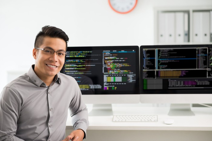 Man smiling in front of computer screen with code on it