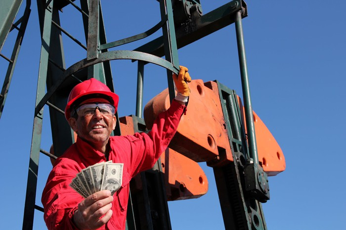 An oil worker on a pump handing out cash.