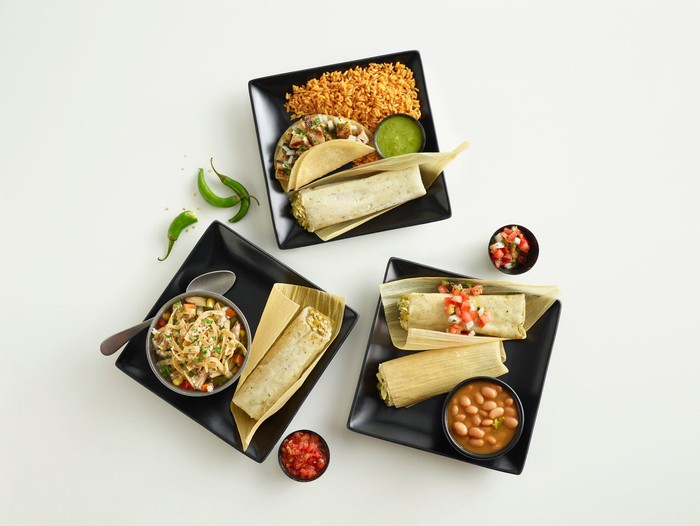 Three platters of El Pollo Loco's tamale special on black plates.