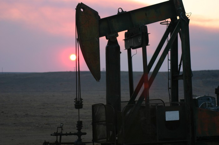 An oil pump with the sun setting in the background.
