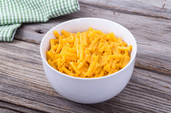 A bowl of mac and cheese on a wooden table