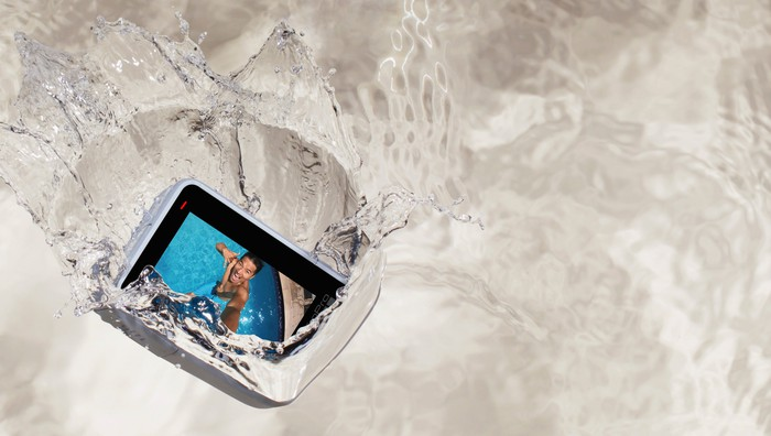 GoPro's HERO7 White camera falling into water with image of smiling man in swimsuit on the display