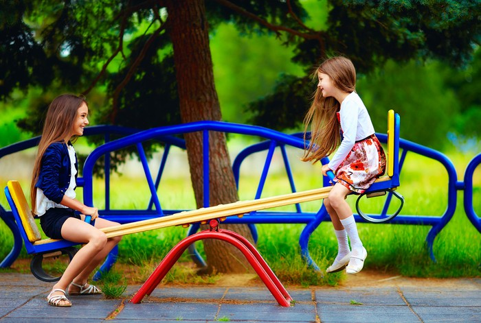 Two girls on a seesaw in the park.
