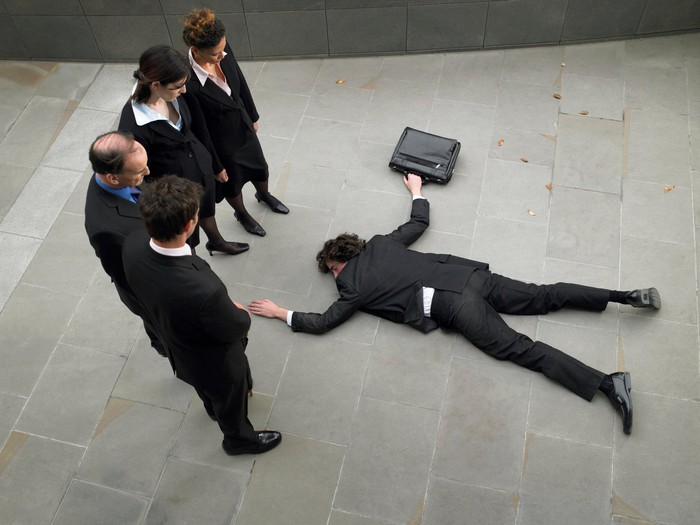 A man wearing a suit and holding a briefcase lies face down on a concrete surface, as if knocked down, while four other people in suits look down at him.