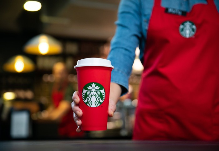 A barista holds a Starbucks holiday cup.