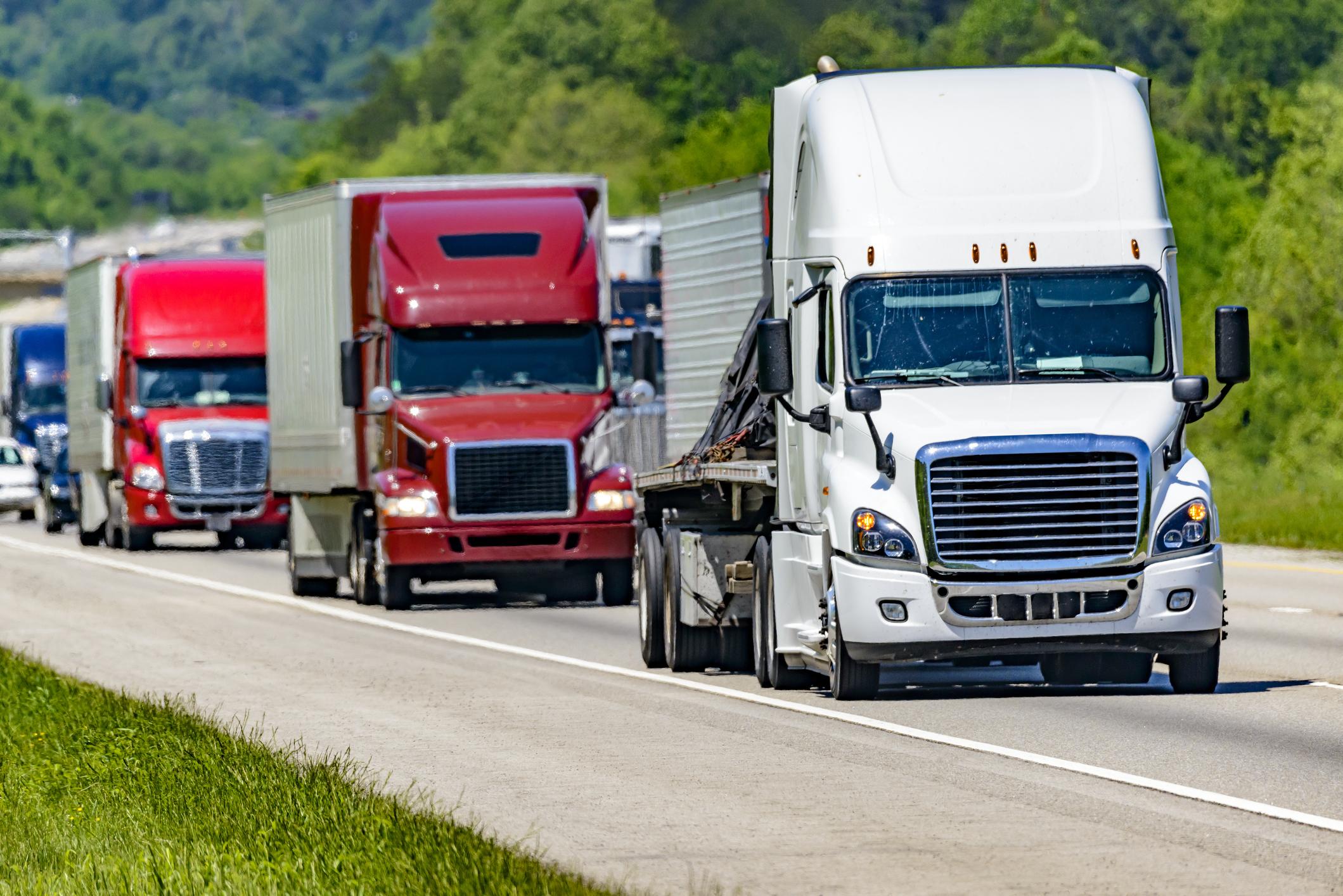 Multiple semi-trucks hauling loads on a highway.
