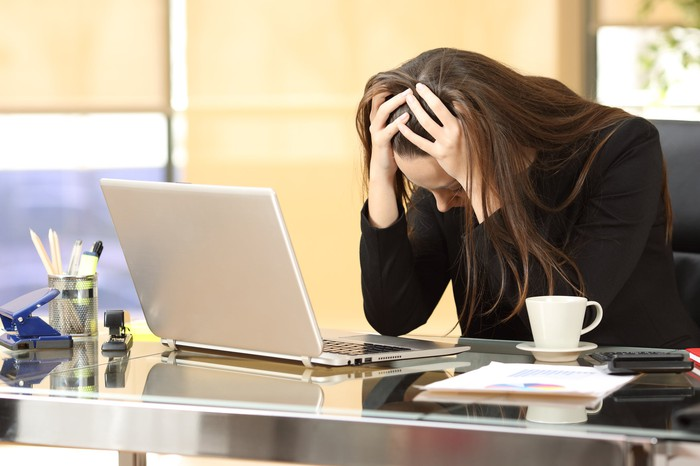 A woman sits at a desk with her head in her hands; a laptop, papers, and a cup are on the desk
