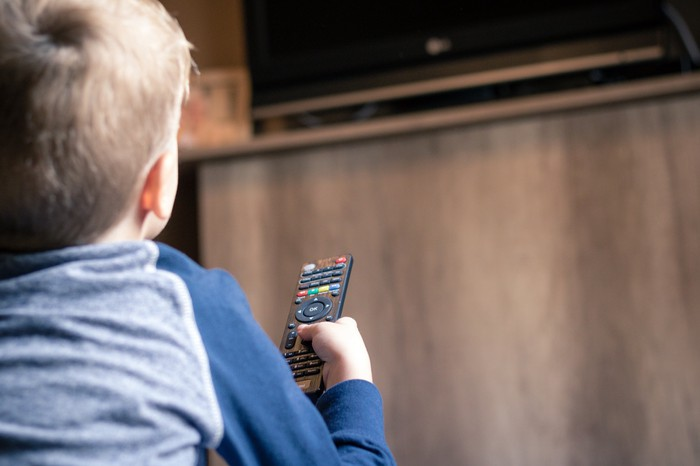 A young boy holding a TV remote.