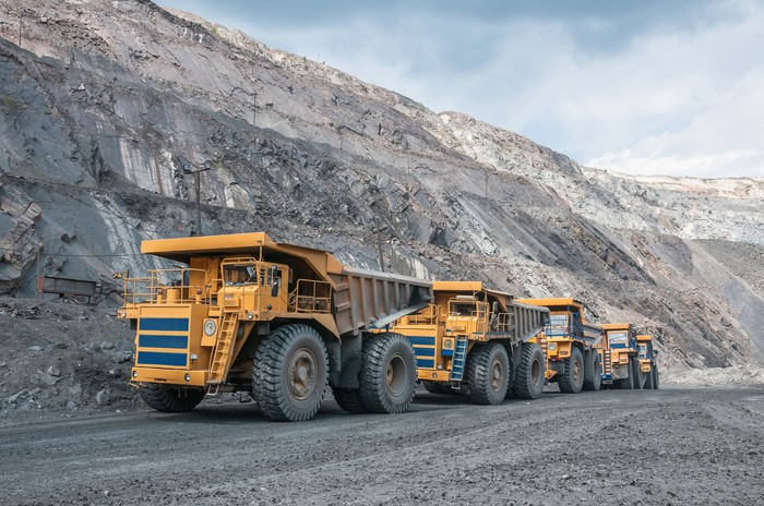 Several trucks drive in a line up a ramp in a mining area.
