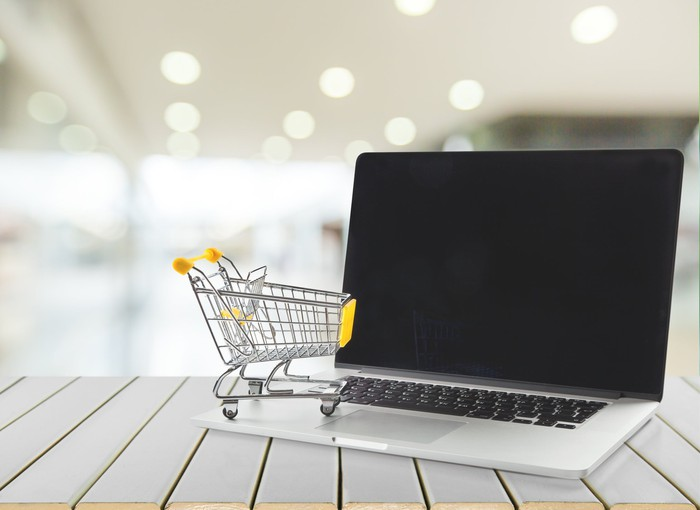 A miniature shopping cart on top of a laptop.