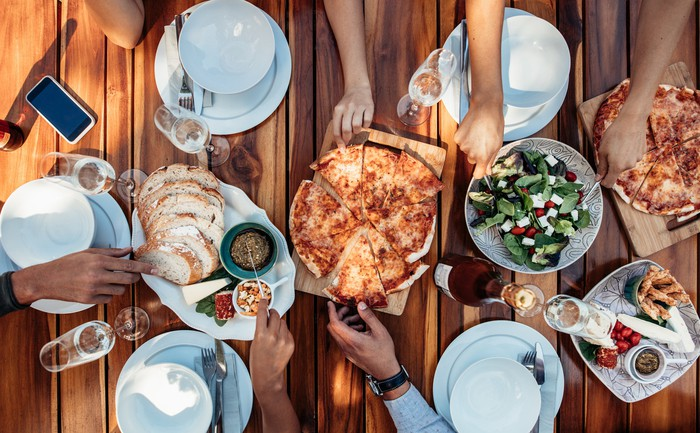 A table with five place settings and six hands reaching out to grab pizza, salad, bread, and other food at the center of the table.