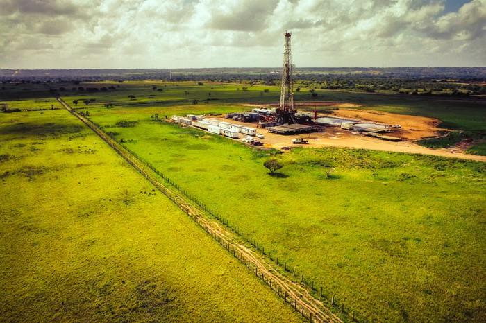 An aerial view of a drilling rig in a field.