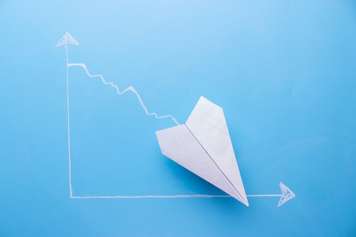 White paper airplane pointing about 45 degrees downward on a light-blue graph background.