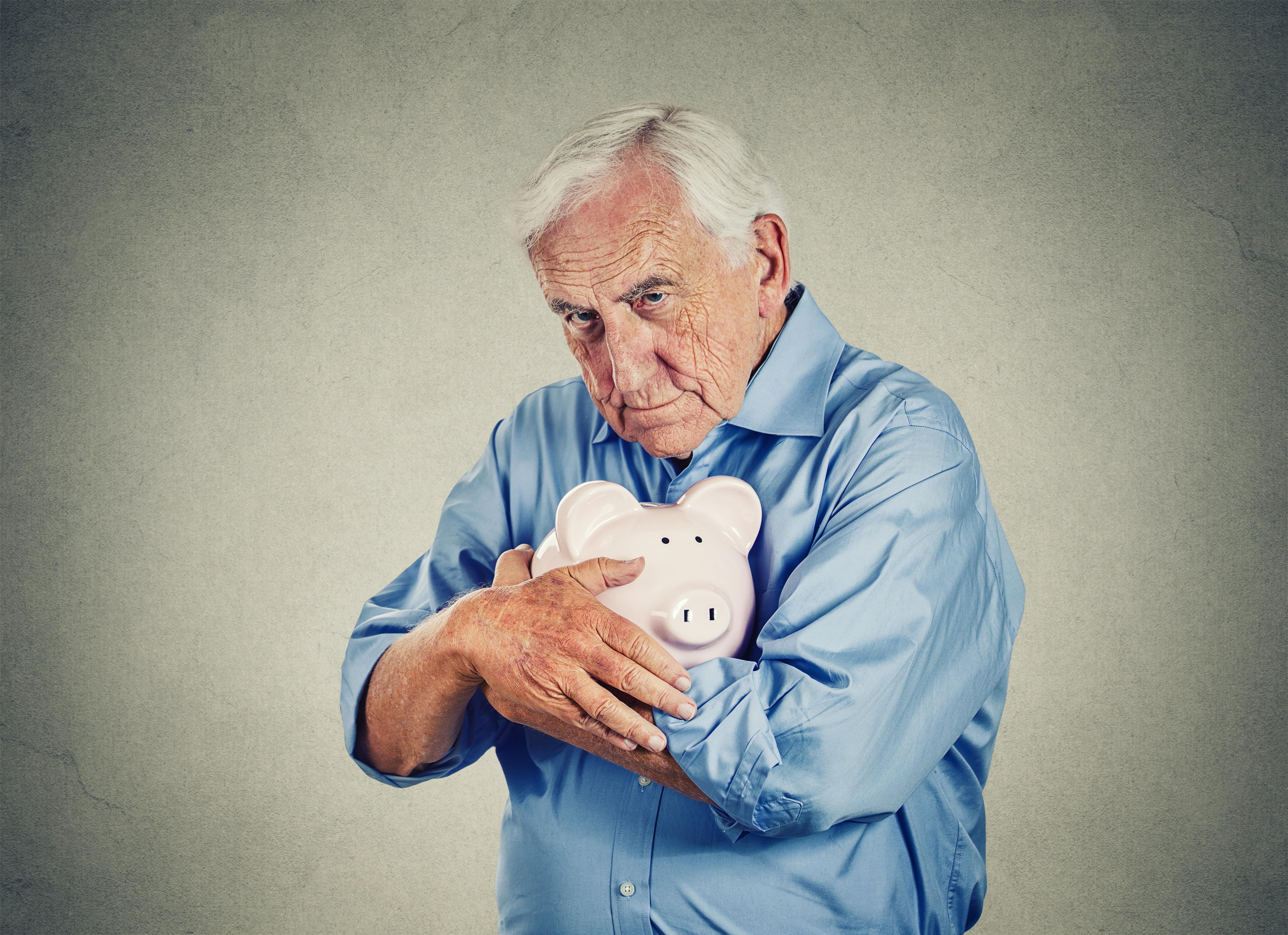 Senior man clutching piggy bank.