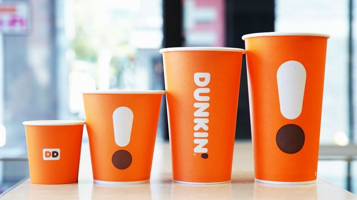Lineup of new orange, minimalistic Dunkin' coffee cups.