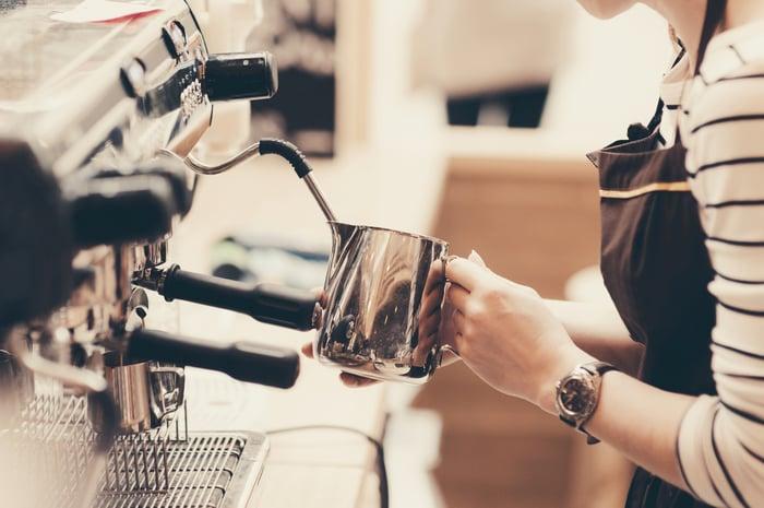 A barista froths milk on an espresso machine.