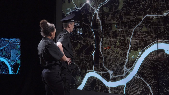 A police coordination team and officers discuss response tactics in front of large live screens in a modern office.
