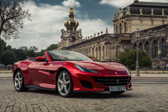 A red Ferrari Portofino, a dramatically-styled convertible sports car, is shown parked in Dresden, Germany.