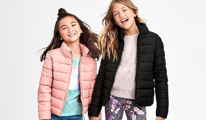 Two smiling girls in jackets, with heads tilted.