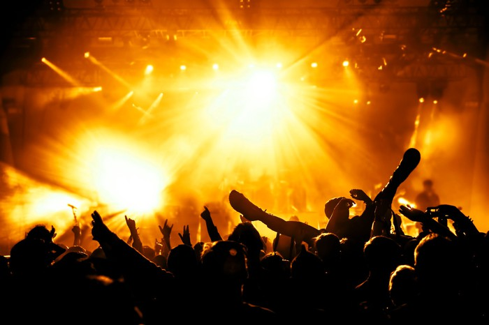 A rowdy crowd at a rock concert, bathed in yellow stage lights.