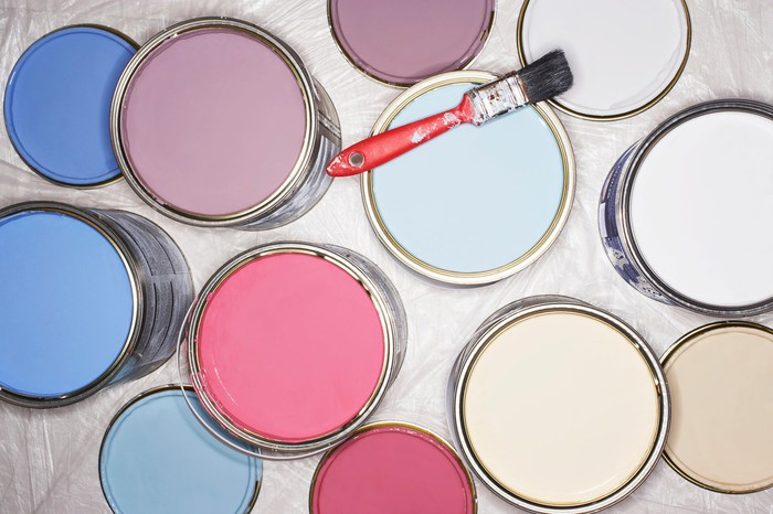 Cans filled with different colors of paint, with a red paint brush on top of one of them.