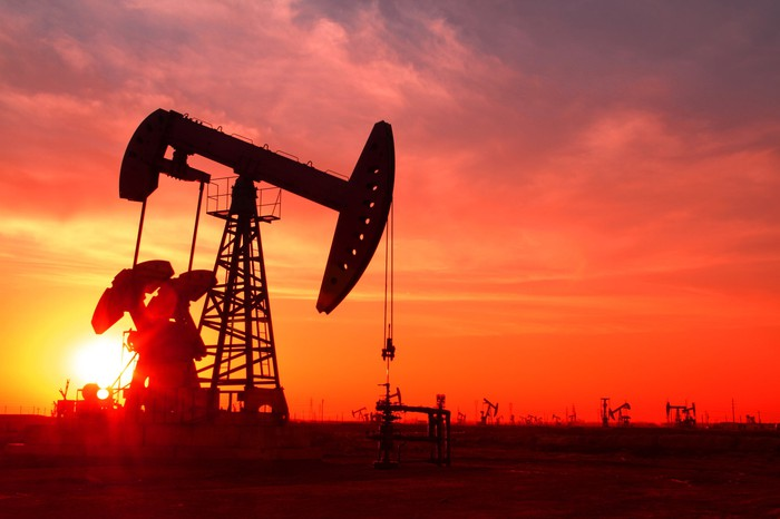 A silhouette of an oil pump in an oil field at sunset.
