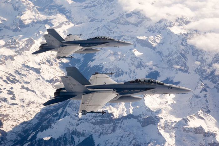 Boeing's F-18 Super Hornet flies over snow-capped mountains.