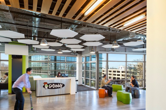 Employees sitting on colorful seats and riding a scooter at GoDaddy headquarters.