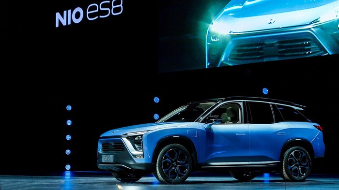 A blue NIO ES8, a midsize electric SUV, on an auto-show stage.